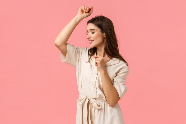 Young woman standing against pink background