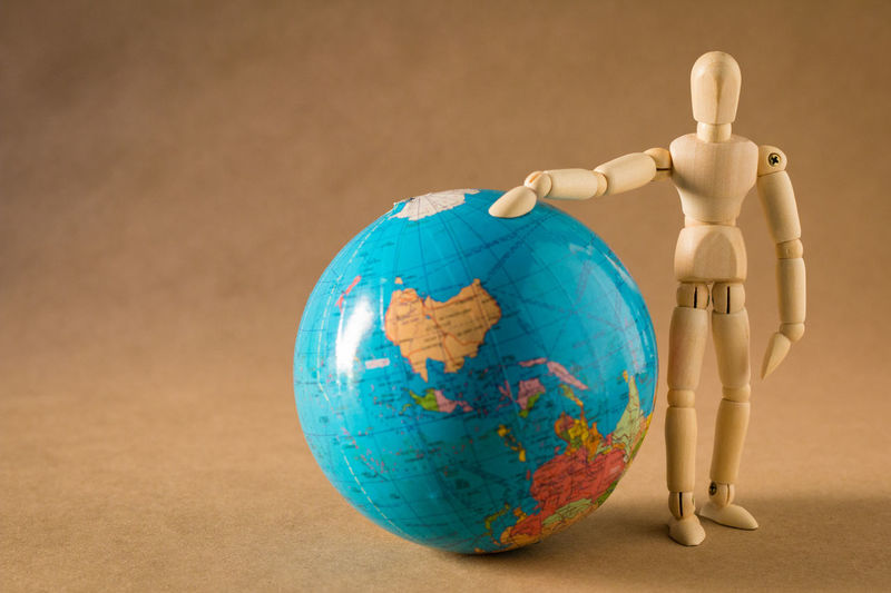 Close up of figurine standing by globe on table