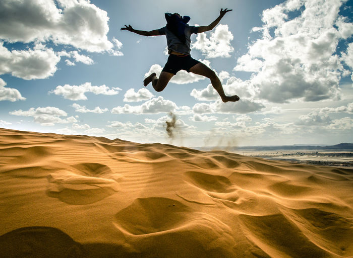 Full length of man jumping on sand