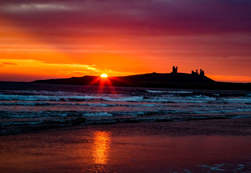 Sunrise over water Dunstanburgh Castle Beauty In Nature Castle Ruin Cloud - Sky Dawn Nature No People Orange Color Outdoors Reflection Scenics Sea Silhouette Sky Sun Sunrise Sunset Tranquil Scene Tranquility Travel Destinations Water Wave