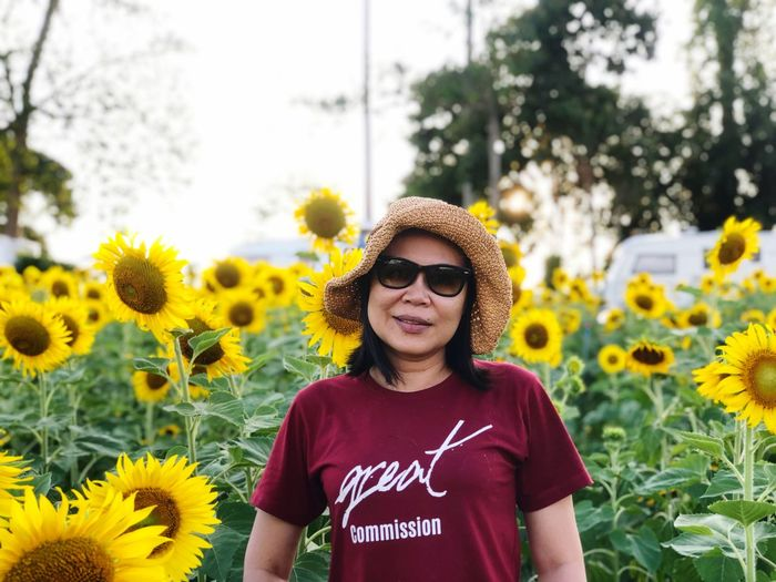 Asian woman standing in the sunflowers field Flower Plant Flowering Plant Yellow One Person Nature Freshness Growth Front View Flower Head Leisure Activity Portrait Real People Lifestyles Fashion Beauty In Nature Day Sunflower Casual Clothing Outdoors