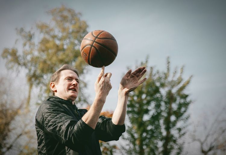 Low angle view of man playing with ball in background