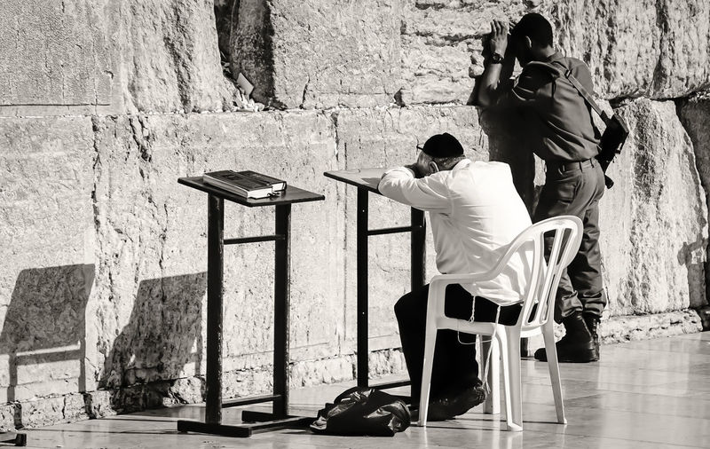 Full length of people praying by wailing wall