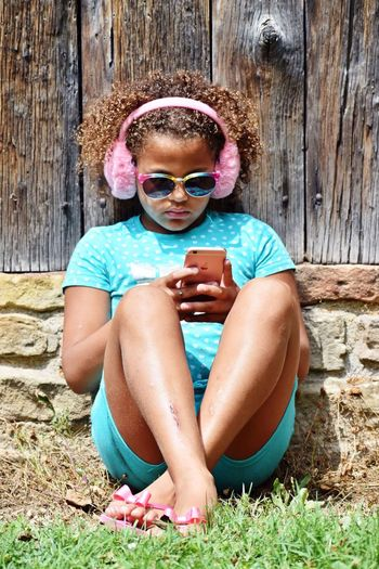Using phone Headphones Phone One Person Glasses Lifestyles Leisure Activity Day Sunglasses Real People Outdoors Childhood Sunlight Casual Clothing Females Nature Girls Fashion Portrait Pink Color Front View Sitting Child