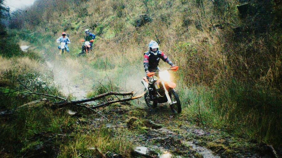 Motocross racer on move through forest