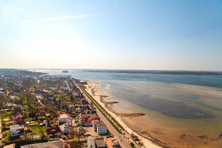 Aerial view of town by beach against sky