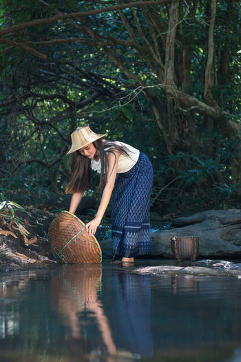 Woman Holding Basket By Pond At Forest