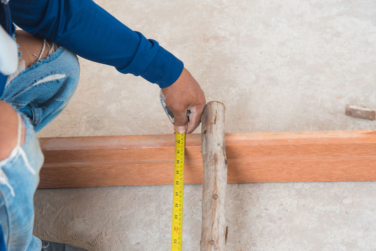 Low section of worker measuring wood