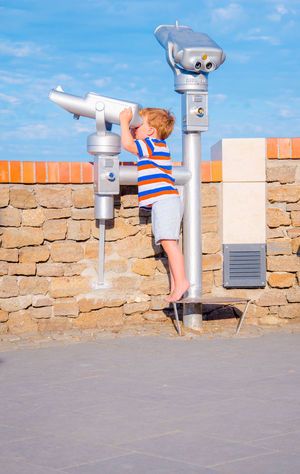 Child looks through telescope on sunny day in summer, vacation scene Beautiful Exploring Observe Architecture Boy Child Childhood Coin-operated Binoculars Color Explorer Hand-held Telescope Kid Little Looking One Person Outdoors People Sky Standing Summer Telescope Vacation Breathing Space