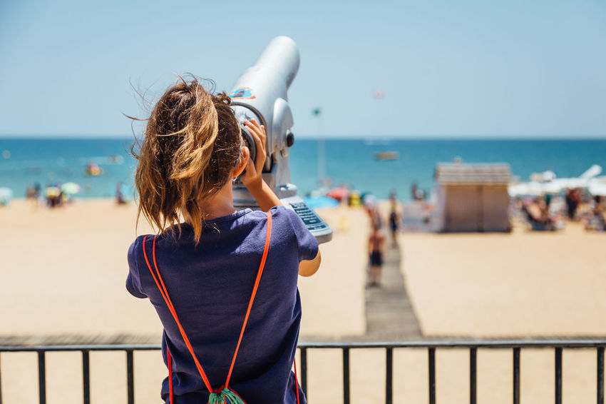 Looking at the sea through binoculars Algarve Beach Binocular View Binoculars Casual Clothing Focus On Foreground Girl Hairstyle Horizon Horizon Over Water Land Leisure Activity Lifestyles Nature One Person Real People Sea Sky Standing Summer Water