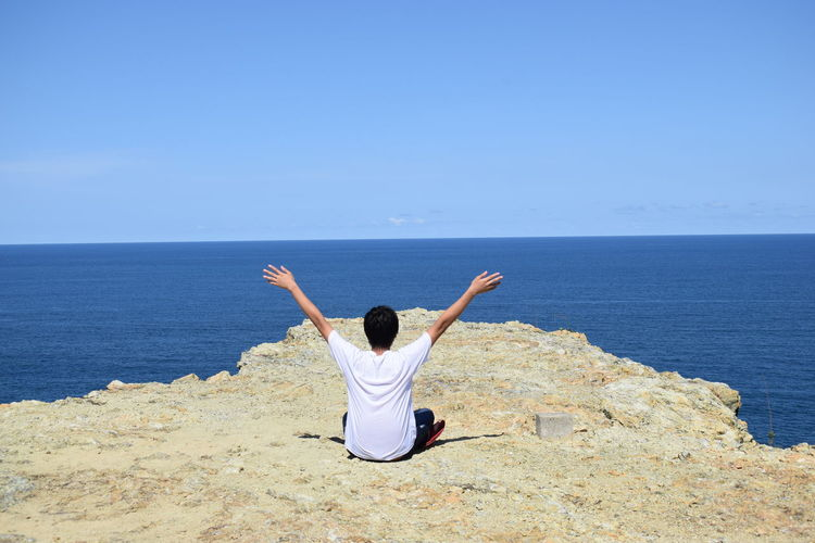 Rear View Of Man With Arms Raised Sitting On Cliff By Sea Against Clear Sky