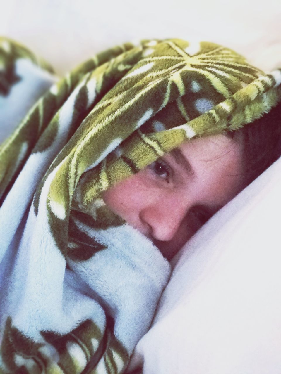 CLOSE-UP PORTRAIT OF CUTE BOY LYING ON BED