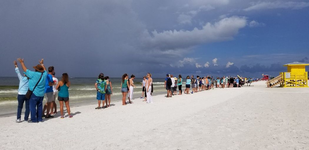 People shore at beach against sky