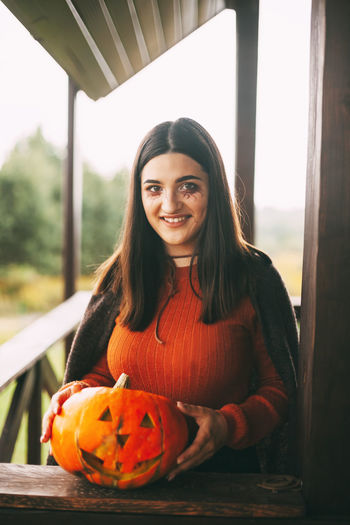 A beautiful girl with dark hair with makeup for the celebration of halloween holds a pumpkin
