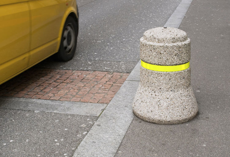 passing car and street bollard Security Sidewalk Urban Scene Bollard Car Cement Close-up Day No People Obstruction Passing Road Safety Street Transportation Yellow