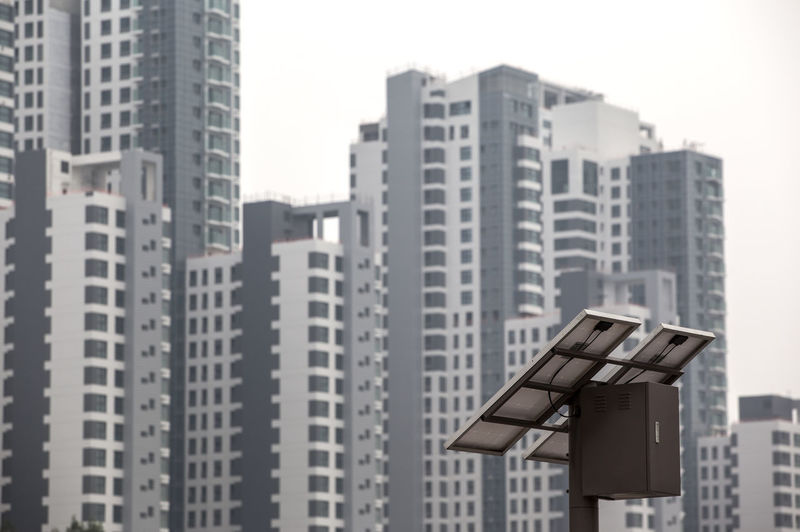 Low angle view of solar panel by buildings in city