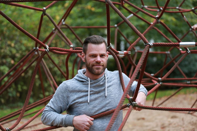 Portrait of man standing amidst jungle gym at playground