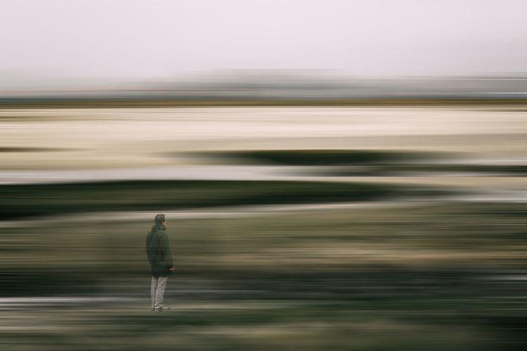Blurred motion of man walking on road