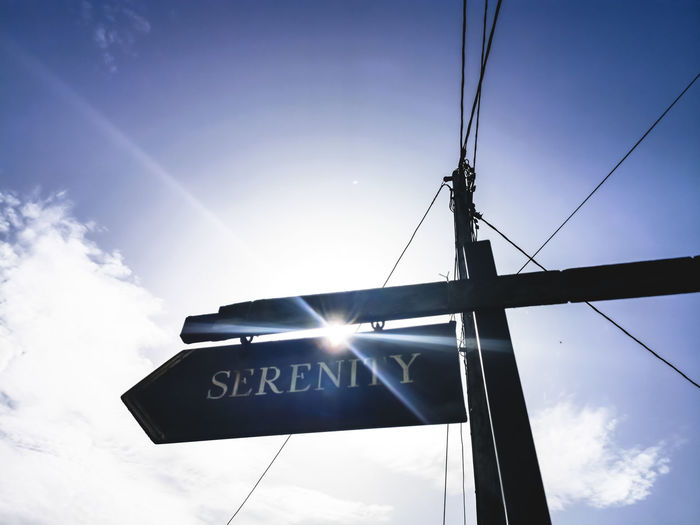 Low angle view of information sign against sky