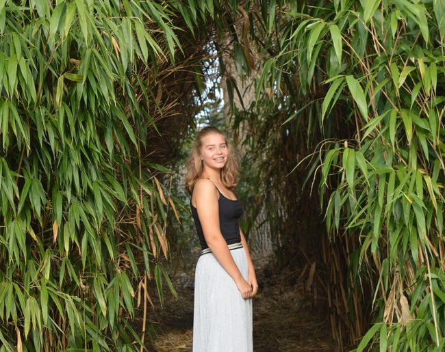 Side view portrait of happy teenage girl standing amidst plants