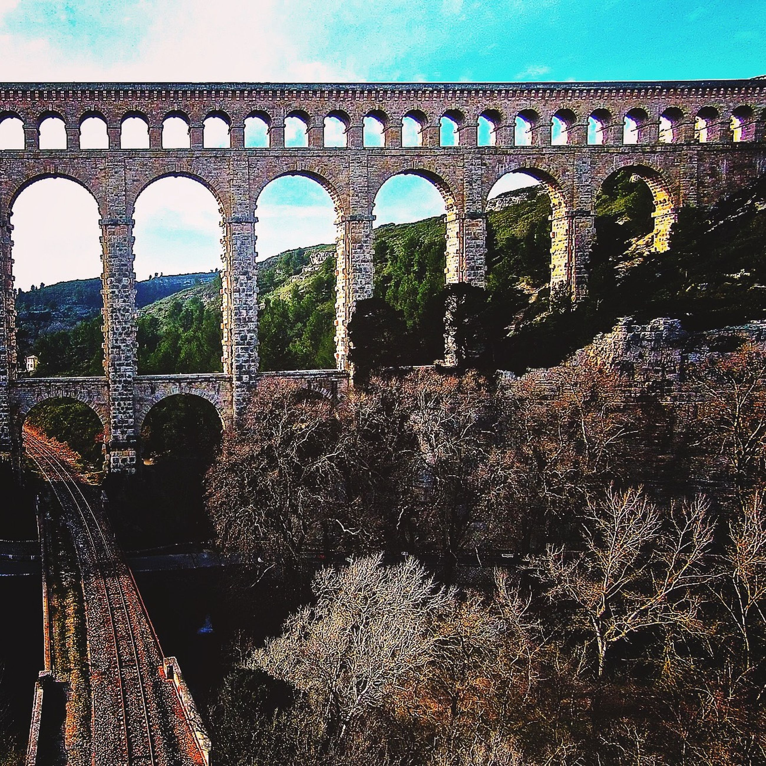 architecture, built structure, arch, bridge - man made structure, connection, arch bridge, sky, bridge, history, architectural column, engineering, low angle view, river, no people, outdoors, day, water, clear sky, nature, travel destinations