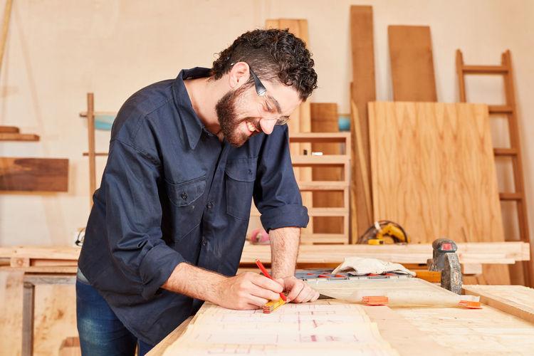 Smiling carpenter working at workshop