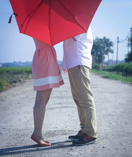 Low Section Of Couple With Red Umbrella Standing On Road