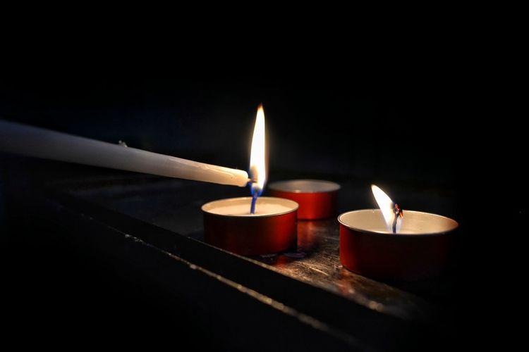 Close-up of illuminated tea light candles in darkroom