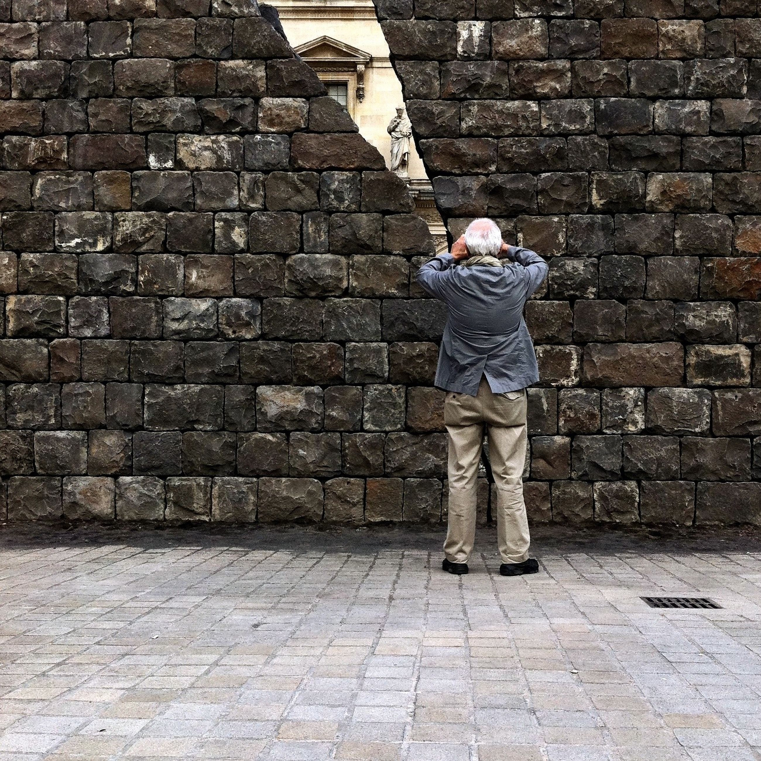 full length, lifestyles, brick wall, casual clothing, cobblestone, rear view, standing, wall - building feature, leisure activity, built structure, architecture, stone wall, walking, building exterior, men, sidewalk, paving stone, day