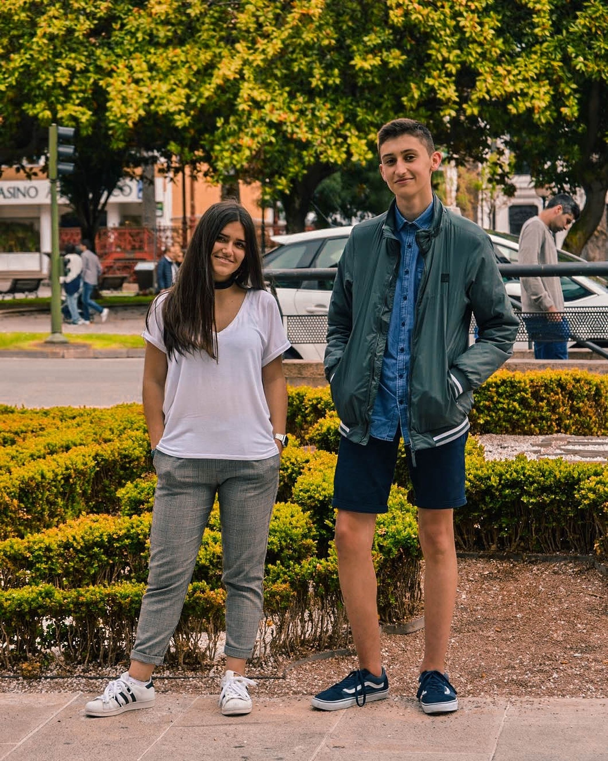 full length, two people, smiling, togetherness, front view, outdoors, happiness, casual clothing, looking at camera, young adult, portrait, day, young women, love, lifestyles, cheerful, friendship, standing, bonding, real people, tree, men, adult, people, adults only