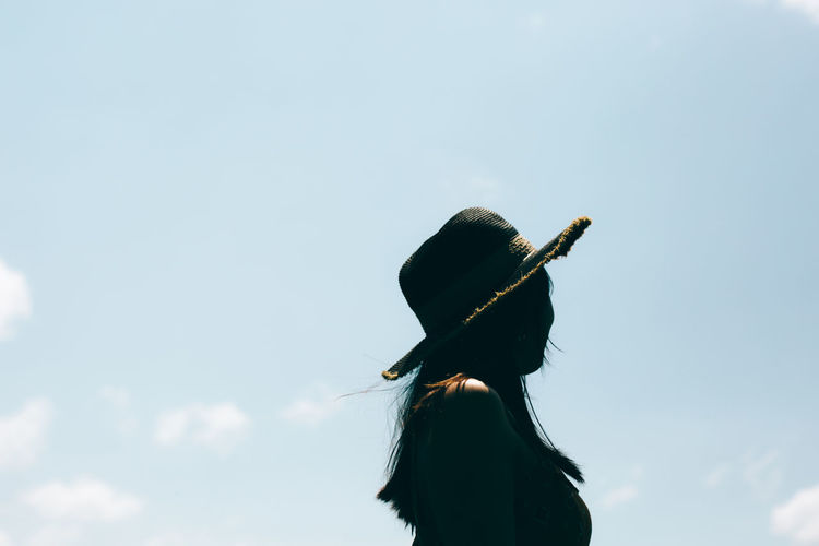 Low angle view of woman standing with umbrella against sky