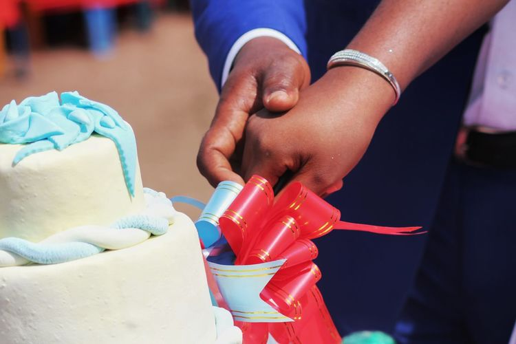 Close-up of couple cutting cake