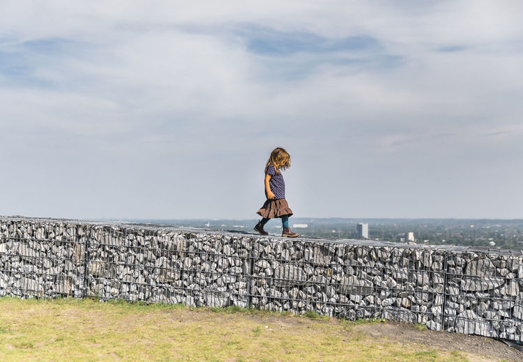 Full length of woman standing on wall against sea