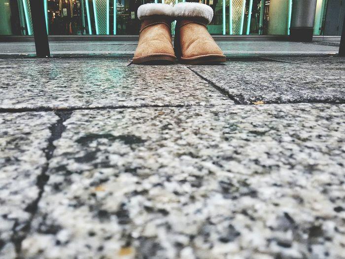 Selective focus of shoes on walkway