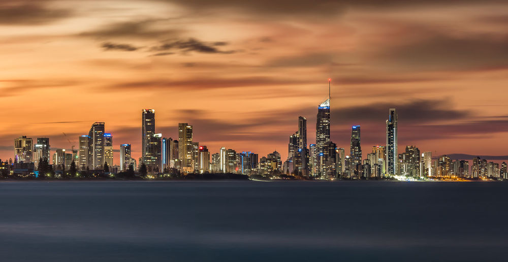 Illuminated modern buildings in city by sea against sky during sunset