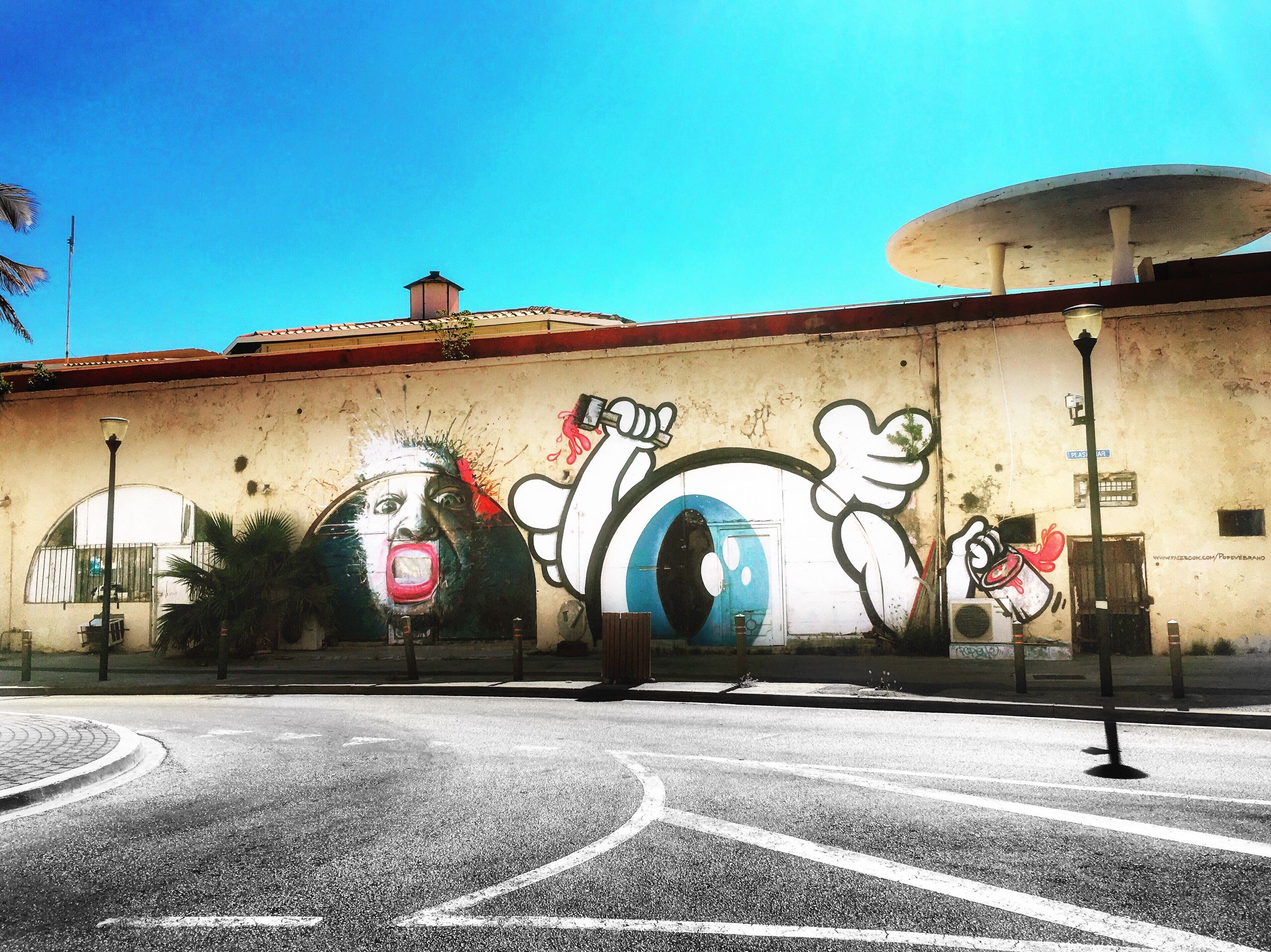 architecture, built structure, building exterior, clear sky, graffiti, multi colored, wall - building feature, art, transportation, road, creativity, blue, outdoors, day, mural, no people, arched, colorful
