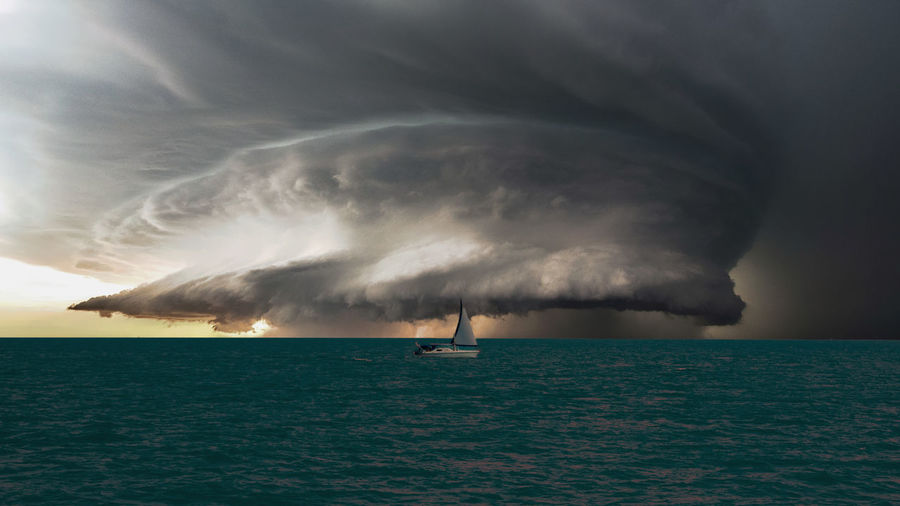 Scenic view of sea against storm clouds during sunset