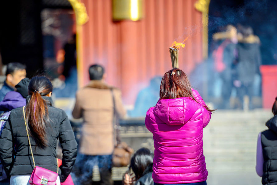 Worshippers hold incense sticks and pray at Yonghegong Lama Temple in Beijing, China. ASIA Beijing Lama Temple Monastery Smoke Worshippers Adult Budhism China Clothing Day Focus On Foreground Group Group Of People Hair Hairstyle History Incidental People Lama Leisure Activity Lifestyles Medium Group Of People Men Mixed Age Range Outdoors People Pink Color Prayer Purple Real People Rear View Religion Stick Temple Women Yonghe Yonghegong