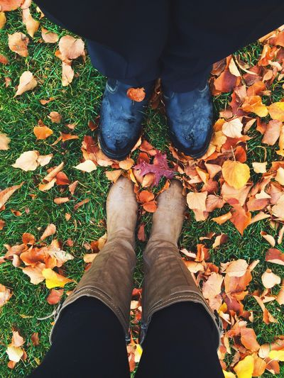Low section of people wearing boots standing on field during autumn