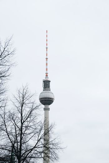 Low angle view of communications tower in city against sky