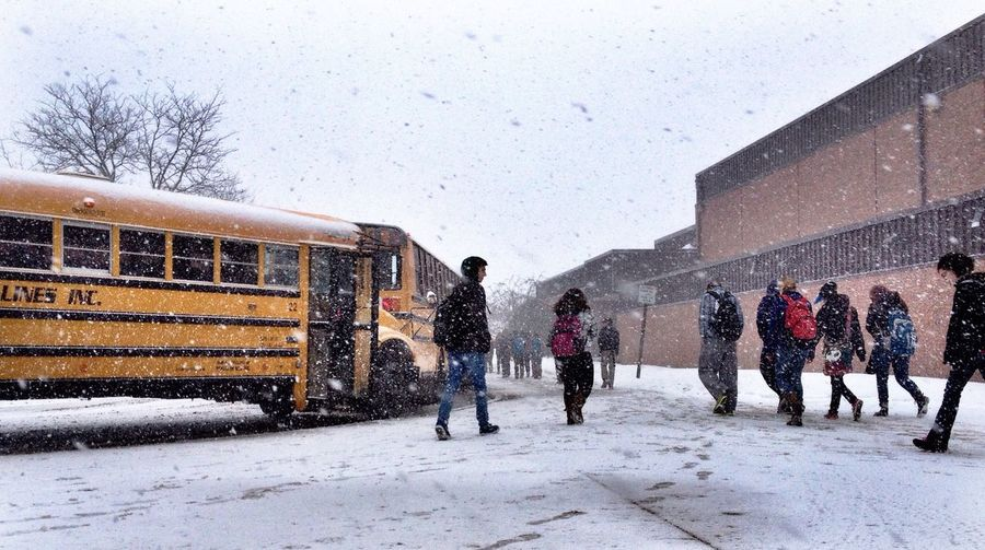 Students walking towards school building while snowing