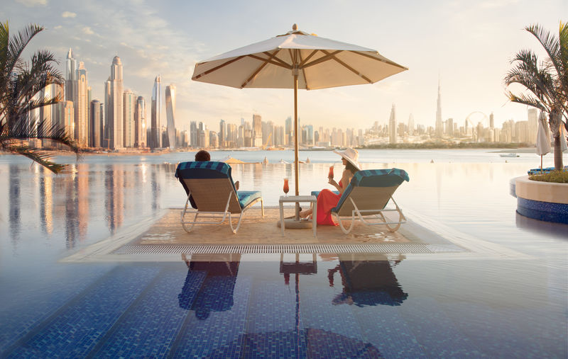 Beautiful beach in Dubai with a lady in red and white hat and her partner, 2 sun chairs and an umbrella. In the background is the skyline of Dubai Marina Water Chair Sitting Full Length Pool Reflection Swimming Pool Adult Nature Real People Seat Leisure Activity Two People Lifestyles Relaxation Women Lounge Chair Sky Day Couple - Relationship Dubai Skyline Skyscraper UAE Holiday