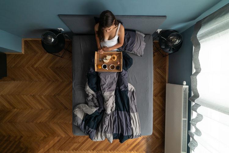 High angle view of woman standing on hardwood floor at home