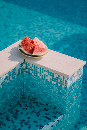 Close-up of watermelon in plate by swimming pool
