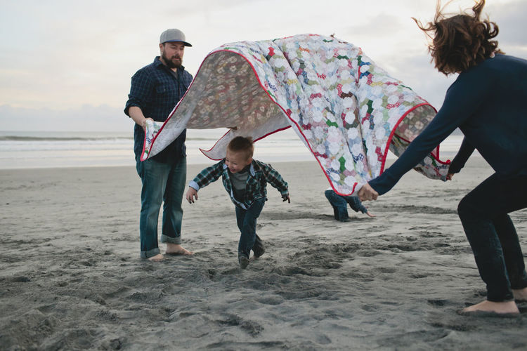 Boy running under picnic blanket held by parents at beach