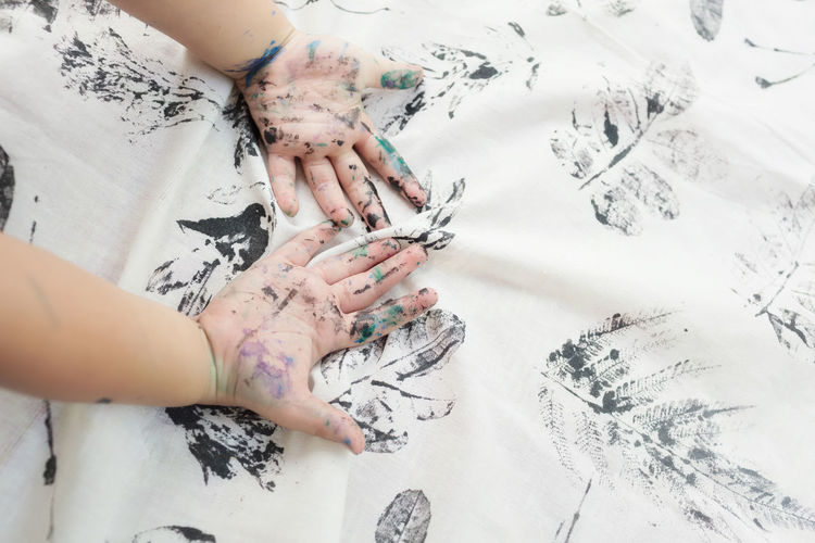 Cropped hands of child hand painting on textile