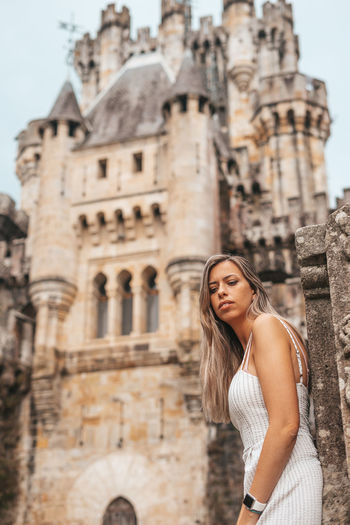 Young woman looking away while standing against historic building
