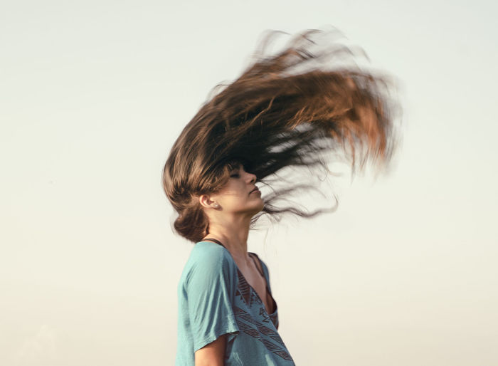 Young woman tossing brown hair against clear sky
