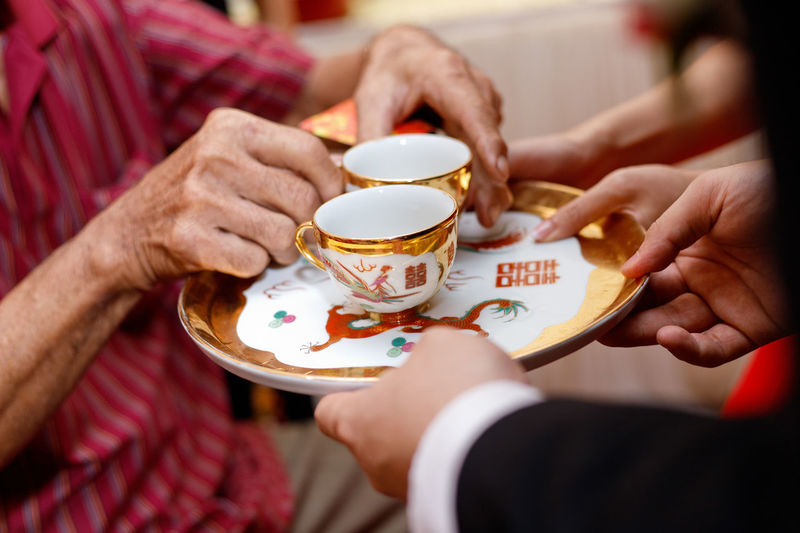 Chinese wedding tea ceremony serving to elders Human Hand Cup Hand Drink Refreshment Holding Food And Drink Human Body Part Hot Drink Midsection Adult Crockery Saucer Women People Tea Tea Cup Tea - Hot Drink Chinese Culture Wedding Ceremony Tea Ceremony Serving Size Elders Culture Bride And Groom