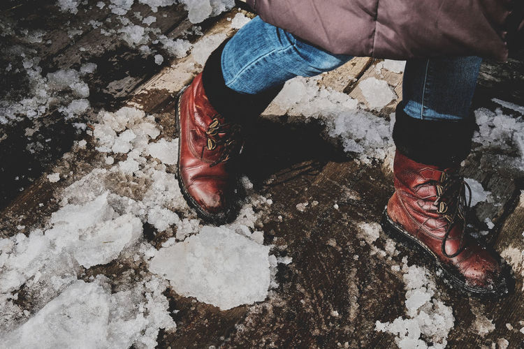 Low section of man walking on footpath with snow